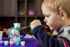 Boy painting ceramic figure Stock Photo