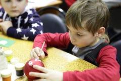 Boy painting Christmas ball Stock Photo