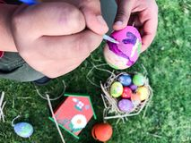 Boy is painting Easter egg at the green garden Royalty Free Stock Images