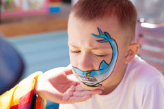 Boy painting face with shark. Stock Photos