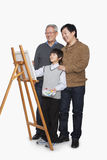 Boy painting with father and grandfather, studio shot Stock Photography