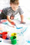 Boy painting, focus on cans Royalty Free Stock Photography