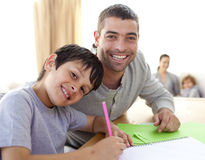 Boy painting with his father at home Stock Photo
