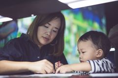 A boy is painting with his mom. A boy is painting with his mom in a dark room Stock Photos