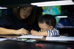 A boy is painting with his mom. A boy is painting with his mom in a dark room Stock Image