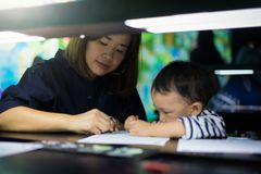 A boy is painting with his mom. A boy is painting with his mom in a dark room Stock Photography