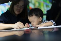 A boy is painting with his mom. A boy is painting with his mom in a dark room Stock Photo