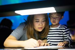 A boy is painting with his mom. A boy is painting with his mom in a dark room Royalty Free Stock Images