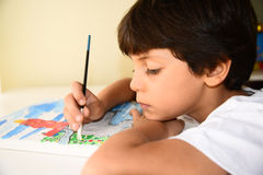 Boy painting and holding the brush Stock Photos