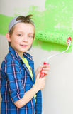Boy is painting interior wall of home. Smiling boy painting interior wall of home Stock Images