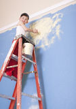 Boy Painting on a Ladder. Young boy standing on a ladder painting a blue wall royalty free stock image