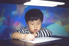 A boy is painting with low light. stock image