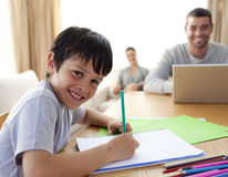 Boy painting and parents working at home. Smiling boy painting and parents working at home Stock Photos