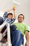 Boy painting the room with his father Stock Image
