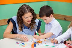 Boy Painting While Teacher Assisting Him. Little boy painting while teacher assisting him at classroom desk Stock Photography