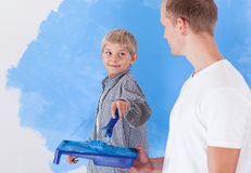 Boy painting wall with father Stock Images