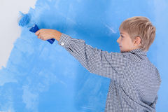 Boy painting wall in his room Stock Photos