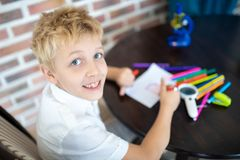 Boy is painting on a white sheet of paper royalty free stock image