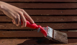 Boy painting wooden coffee table with brush.  Royalty Free Stock Photography