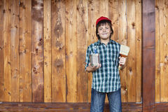 Boy painting wooden wall Stock Photo