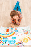 Boy painting. Young boy relaxing while painting with watercolors lying on the floor Stock Photo