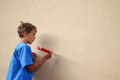 Boy paints by big pencil on wall Royalty Free Stock Image