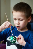 Boy paints a Christmas ball toy Royalty Free Stock Images