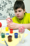 Boy paints the Easter eggs with a brush Royalty Free Stock Photos