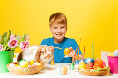 Boy paints Easter eggs with cute rabbit on  table Stock Image