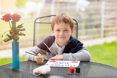 Boy paints greeting card for Mom Royalty Free Stock Images