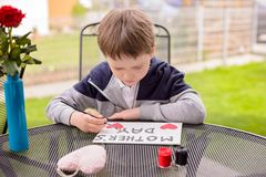 Boy paints greeting card for Mom Stock Photo