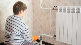 Boy paints a heating radiator in  apartment stock video
