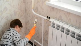 Boy paints a heating radiator in  apartment stock video footage