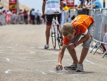 Boy Paiting the Road. Mont Ventoux, France- July 14 2013: A boy paiting the road to Mont Ventoux while amateur cyclists climb few hours before the apparition of Stock Photos