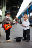 Boy, paling on a quitar. On  arailway station Stock Image
