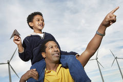 Boy With Paper Plane Sitting On Father's Shoulders. Little boy with paper plane sitting on father's shoulders at wind farm Royalty Free Stock Photography