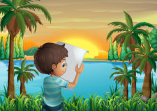 A boy with a paper at the riverbank Stock Photography