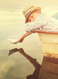 Boy with paper ship in old boat Royalty Free Stock Images