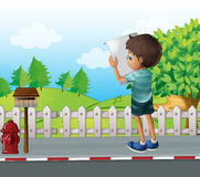 A boy with a paper standing near the fence at the street Royalty Free Stock Images