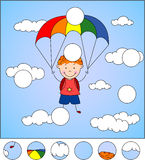 Boy parachutist descends from the sky on a parachute through the Stock Photography