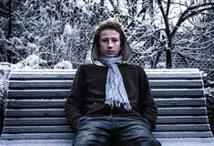 Boy on park bench in winter