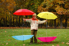 Boy in park control over four umbrellas Royalty Free Stock Photography