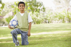 Boy in park holding football Stock Photo