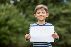 Boy in park holding placard that reads alphabets Stock Photography