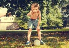 Boy in park ready to kick ball Stock Image