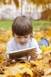 Boy in the park using a tablet PC Stock Photography