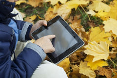 Boy in the park using a tablet PC Royalty Free Stock Image
