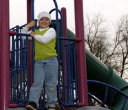 Boy at park with white sock hat. Boy standing on the playground equipment at the park during a break from cold weather royalty free stock photo