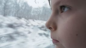 Boy in the passenger car looking out through the train window onto snow covered field and trees. Close Up. Portrait of a boy in the passenger car looking out stock video