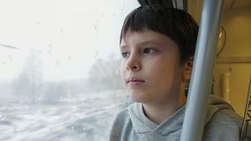 Boy in the passenger car looking out through the train window onto snow covered field and trees. Portrait of a boy in the passenger car looking out through the stock footage